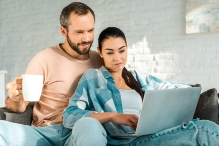 handsome husband holding cup of coffee while wife using laptop on couch