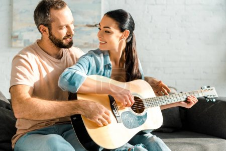 Photo for Husband teaching smiling wife to play acoustic guitar - Royalty Free Image