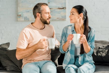 husband and wife sitting on couch, drinking coffee and looking at each other