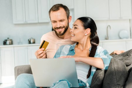 handsome husband holding credit card while smiling wife using laptop and doing online shopping at home