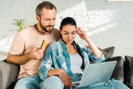 handsome husband holding credit card while beautiful wife using laptop and doing online shopping at home