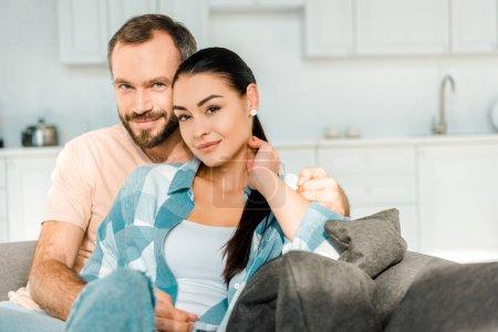 Photo pour Couple heureux regardant la caméra, embrassant et assise sur canapé à la maison - image libre de droit