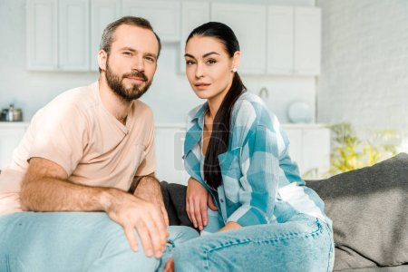 Photo for Beautiful loving couple looking at camera and sitting on couch at home - Royalty Free Image