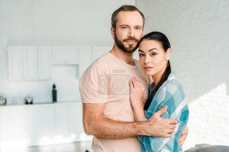 Photo pour Portrait de beau couple embrassant et en regardant la caméra à la maison - image libre de droit