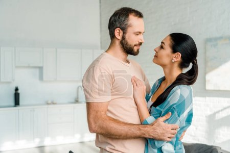 Photo for Portrait of smiling couple embracing and looking at each other at home - Royalty Free Image