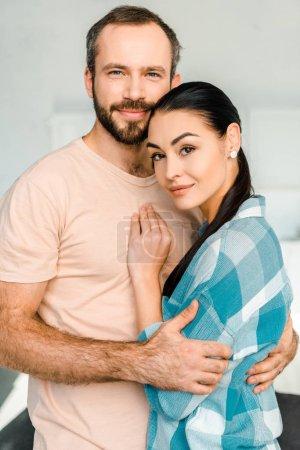 Photo pour Portrait de couple heureux embrassant et en regardant la caméra - image libre de droit
