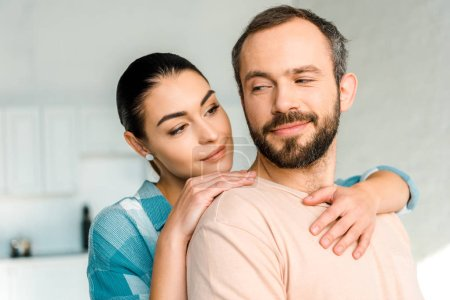 Photo for Portrait of happy wife embracing smiling husband at home - Royalty Free Image