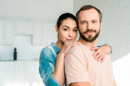 Photo pour Portrait de femme heureux mari embrasser et regardant la caméra - image libre de droit