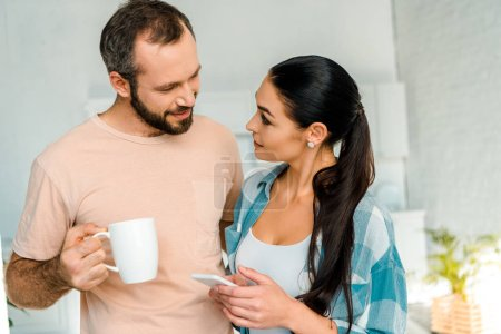 wife using smartphone while smiling husband holding cup of coffee at home