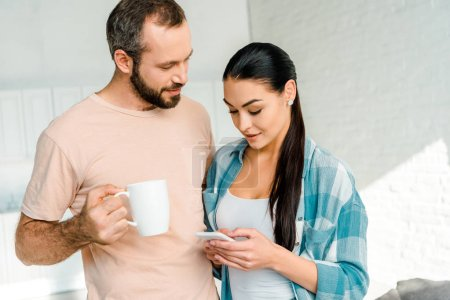 beautiful brunette wife using smartphone while husband holding cup of coffee at home