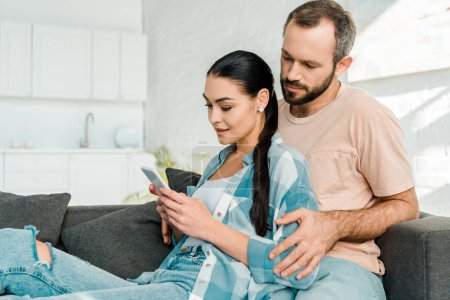 beautiful couple sitting on couch and using smartphone at home