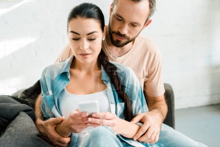 attractive couple sitting on couch, hugging and using smartphone at home