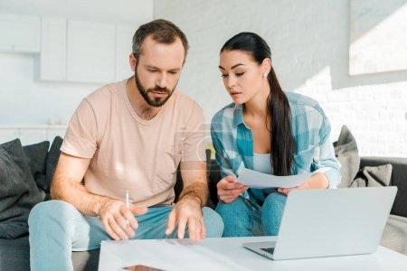 Photo pour Couple concentré assis sur le canapé, remplir les papiers, en utilisant un ordinateur portable et la planification - image libre de droit