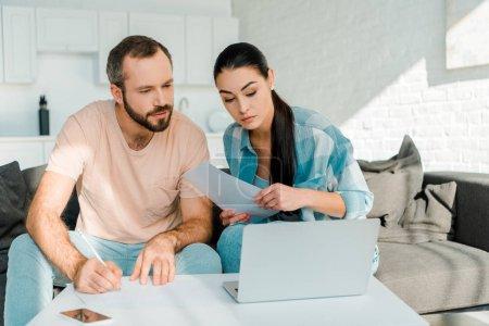 Photo pour Concentré de couple assis sur le canapé, remplissage des documents, à l'aide d'ordinateur portable et la planification - image libre de droit