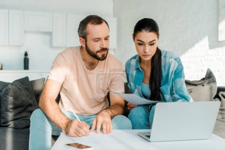 serious couple sitting on couch, filling papers, using laptop and planning at home