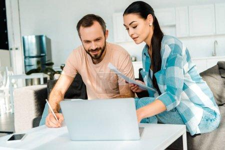 Photo pour Couple assis sur le canapé, remplir les formalités administratives et à l'aide d'ordinateur portable à la maison - image libre de droit