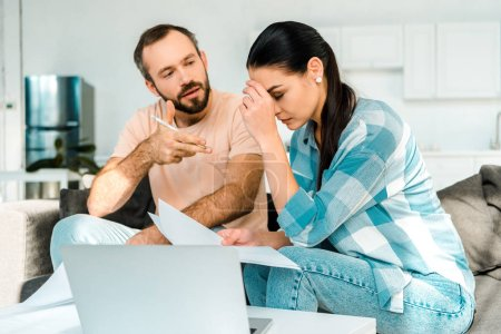 tired couple sitting on couch, using laptop and having financial problems at home