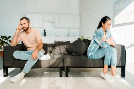 couple having disagreement and sitting at opposite ends of sofa