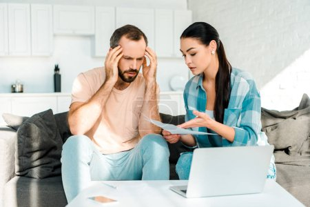 Photo for Stressed couple sitting on couch, using laptop and having financial problems - Royalty Free Image
