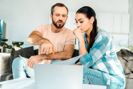 Photo for Couple sitting on couch, using laptop and trying to solve financial problems at home - Royalty Free Image