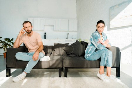 couple having argument and sitting at opposite ends of sofa