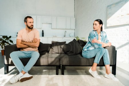 frustrated couple having argument and sitting at opposite ends of sofa