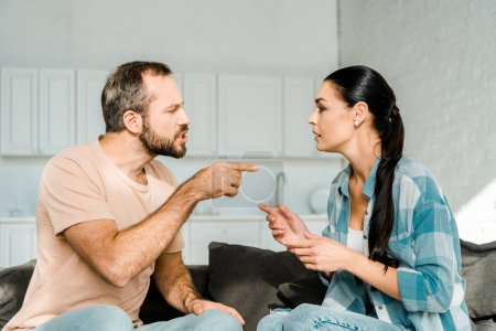 couple having argument and husband yelling at wife at home