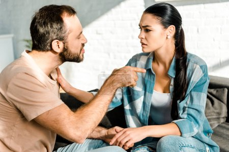 couple having argument and husband insulting wife at home