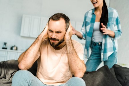 frustrated husband on foreground covering ears with hands and having argument with wife at home