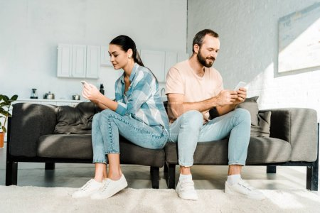 couple sitting on couch, facing opposite direction and using smartphones at home