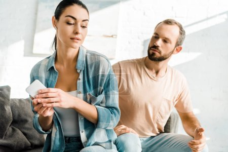 wife holding smartphone and having misunderstanding with dissatisfied husband at home