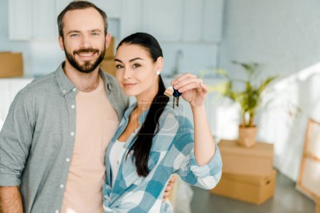 happy couple looking at camera and wife holding keys from new house, moving concept