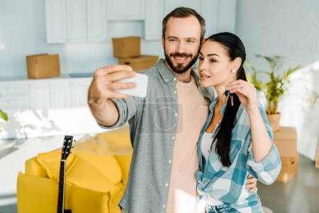 smiling husband taking selfie on smartphone while wife holding keys from new house