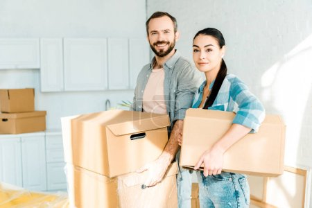 husband and wife carrying cardboard boxes and packing for new house, moving concept