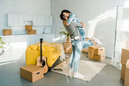 Photo for Happy husband hugging wife while packing for new house, moving concept - Royalty Free Image
