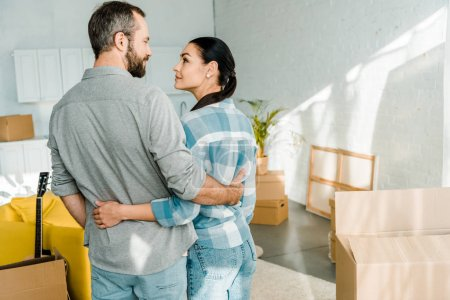 happy couple embracing while packing for new house, moving concept