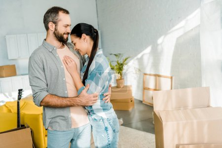 Photo for Laughing couple embracing while packing for new house, moving concept - Royalty Free Image