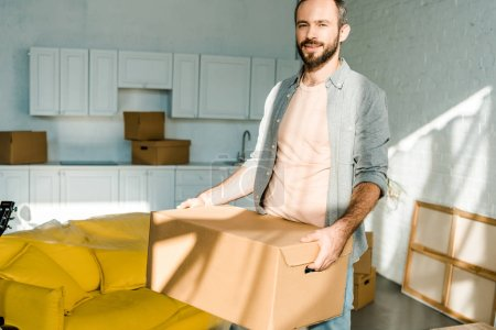 handsome man carrying cardboard box and packing for new house, moving concept
