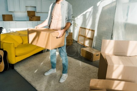 Photo for Cropped view of man carrying cardboard box and packing for new house, moving concept - Royalty Free Image