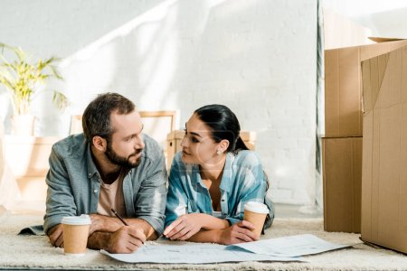 husband and attractive wife lying on floor, drinking coffee and working on blueprints of new house at home, moving concept