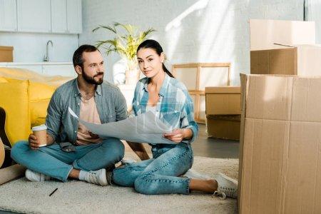 Photo pour Souriant, mari et femme buvant du café et la tenue de plan de maison neuve, se déplaçant de concept - image libre de droit