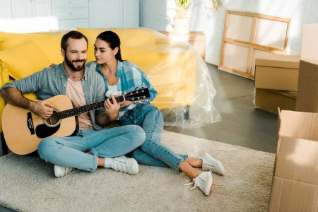 Photo for Handsome husband sitting on floor and playing acoustic guitar while wife listening - Royalty Free Image