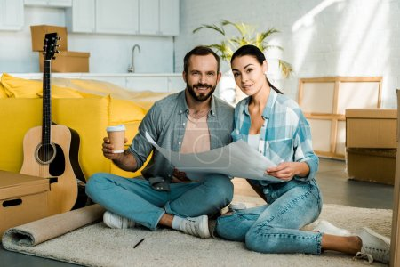 Photo for Handsome husband and wife drinking coffee and holding blueprint of new house, moving concept - Royalty Free Image