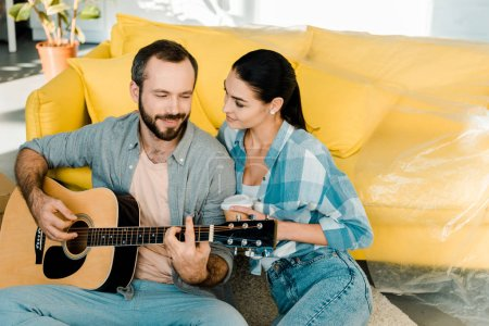 husband sitting on floor and playing acoustic guitar while beautiful wife listening