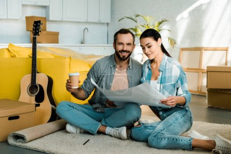 Photo pour Souriant, mari et femme beau boire du café et la tenue de plan de maison neuve, se déplaçant de concept - image libre de droit