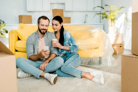 smiling couple drinking coffee, using smartphone and relaxing after packing for new house, moving concept