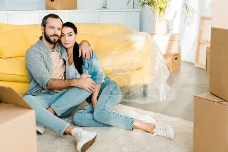 beautiful couple sitting on floor, hugging and relaxing after packing for new house, moving concept