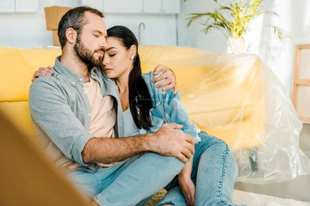 husband and wife sitting on couch and resting after packing for new house, moving concept