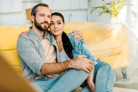 husband and wife sitting on couch after packing for new house, moving concept