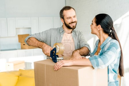 husband and wife packing cardboard box with scotch tape, moving concept